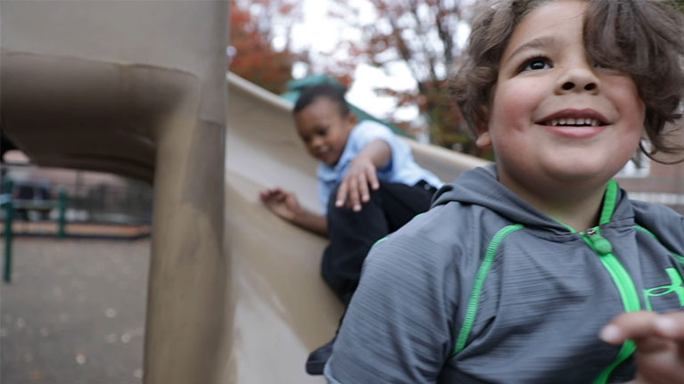 Young boy going down a slide and smiling while looking up