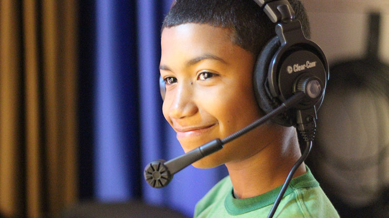 Young boy smiling and wearing a TV headset