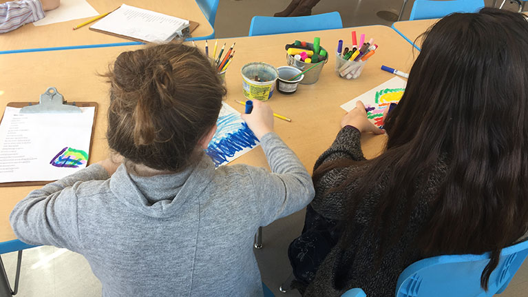 The back of two girls coloring at a desk