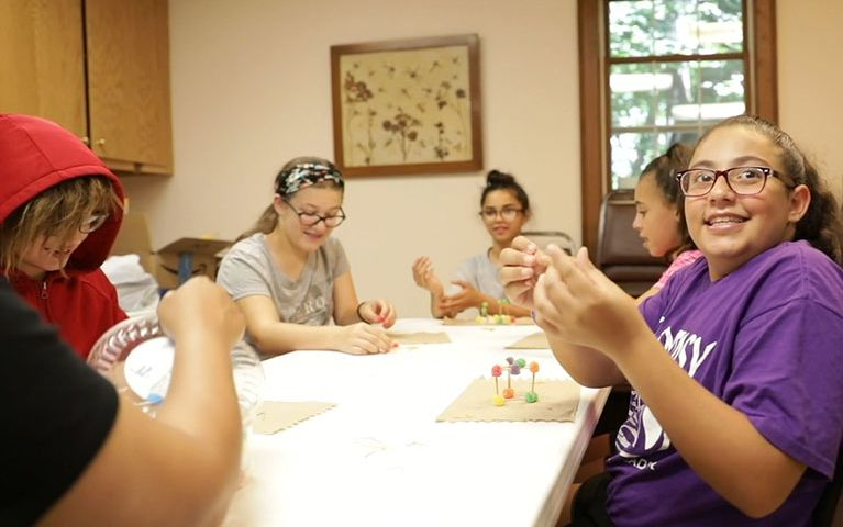 Group of young girls sitting at a table together and crafting