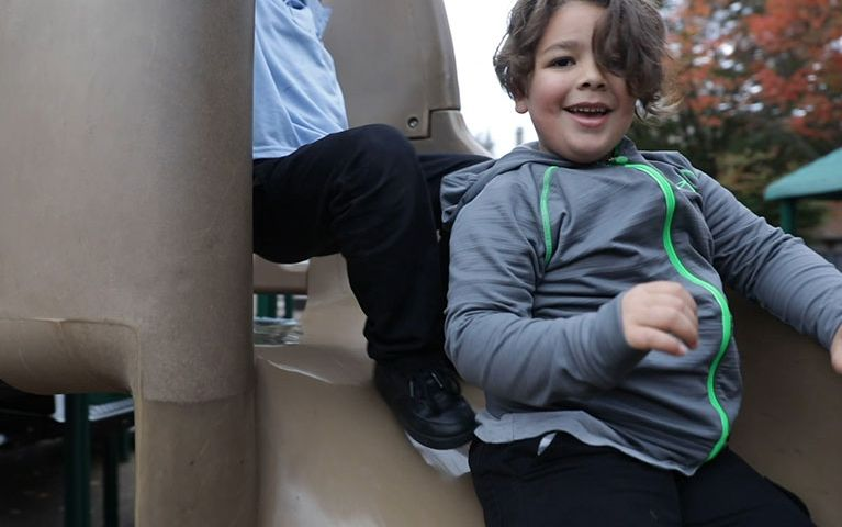 Young boy going down a slide and smiling at the camera